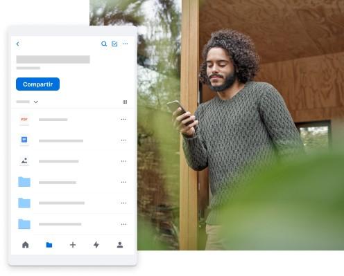 Un hombre en un entorno al aire libre navega por su contenido personal en Dropbox desde su teléfono móvil
