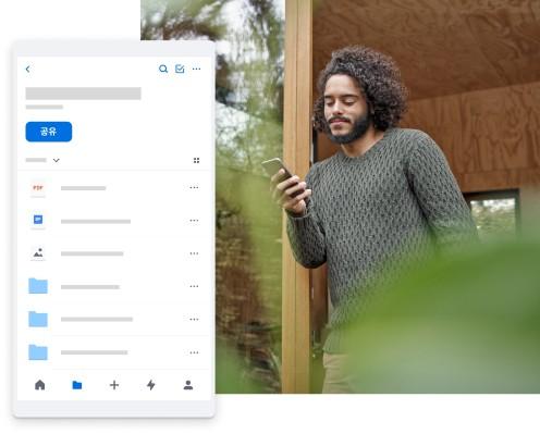 밖에서 휴대폰을 통해 Dropbox에 있는 개인용 콘텐츠를 검색하는 사람