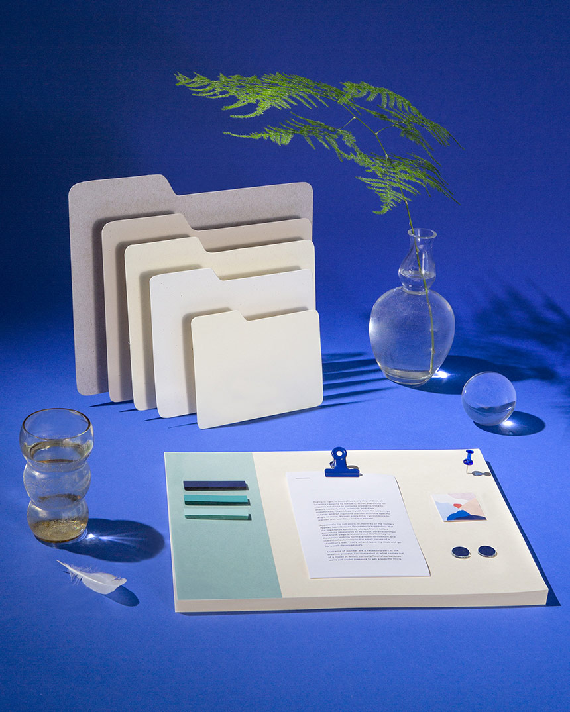 書類をファイリングするための従来のフォルダや文房具が並ぶ、旧式のデスクやワークスペース。